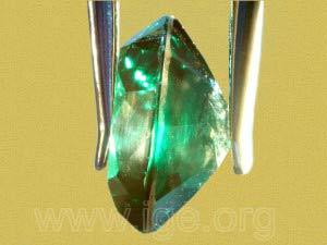 Doblete compuesto de dos partes de espinela sintética incolora, unidas con un pegamento verde. Observación en el aire.